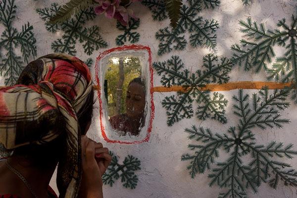 Egy fiatal nő a ház falába épitett tükörben nézi magát. A díszités műfenyő ágakból van. © Anzor Buharsky