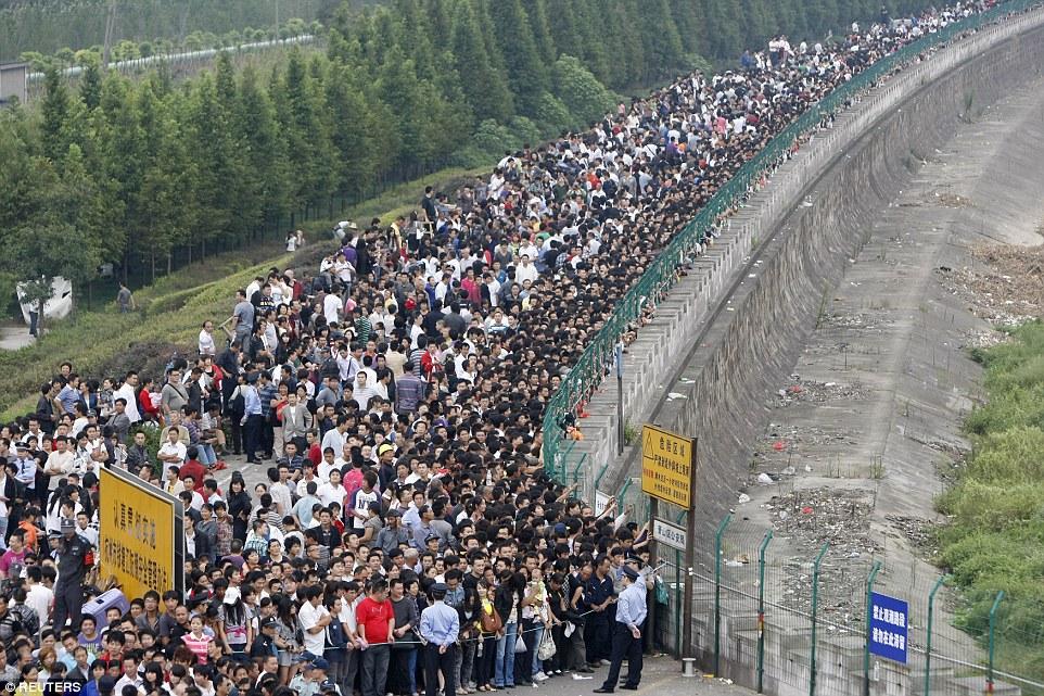 Ezrek várják a torlóárat a Qiantang folyónál Hangzhouban, Zhejiang tartományban 2010-ben