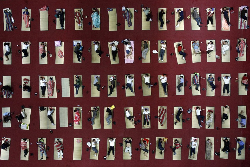Egyetemisták alszanak a tornaterem padlóján Wuhanban, Hubei tartományban mert a kollégiumi szobákban nincs légkondícionáló