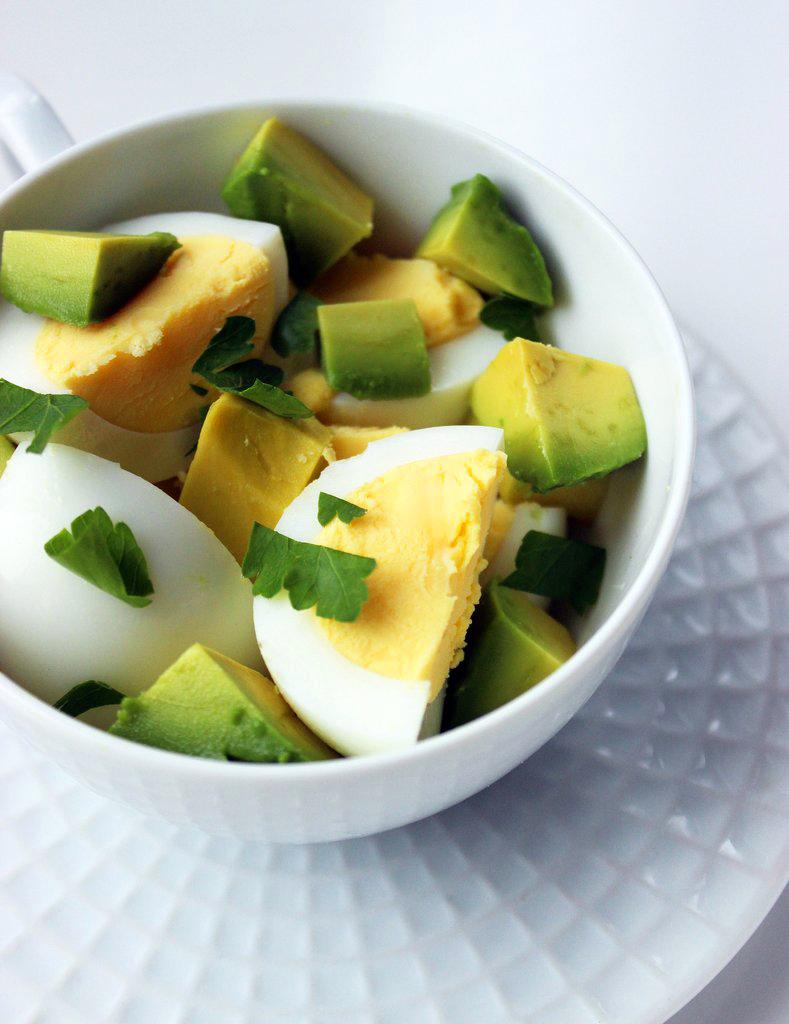 Tojásos avokádósaláta hozzávalói: két tojás keményre főzve, fél avokádó felszeletelve, egy evőkanál friss petrezselyem.