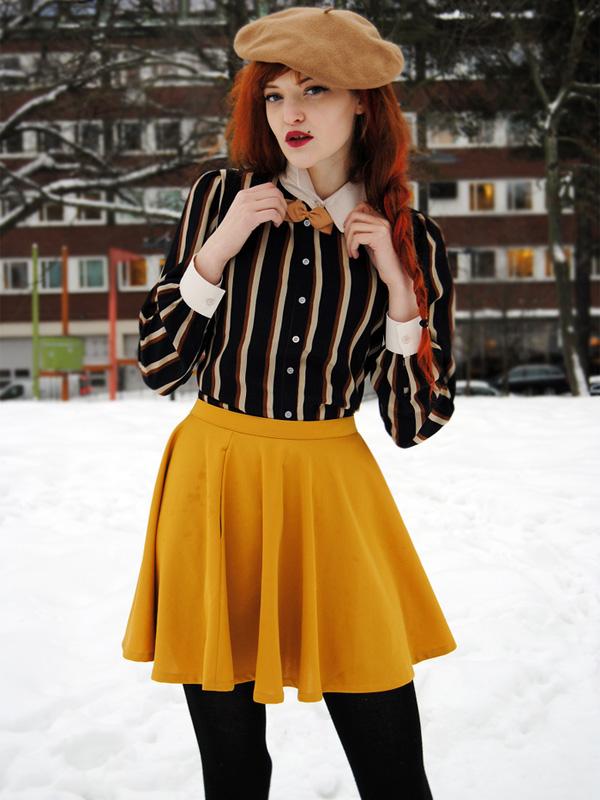 Fekete harisnyával, csizmával és blúzzal a mustársárga szoknya elképesztően stílusos.