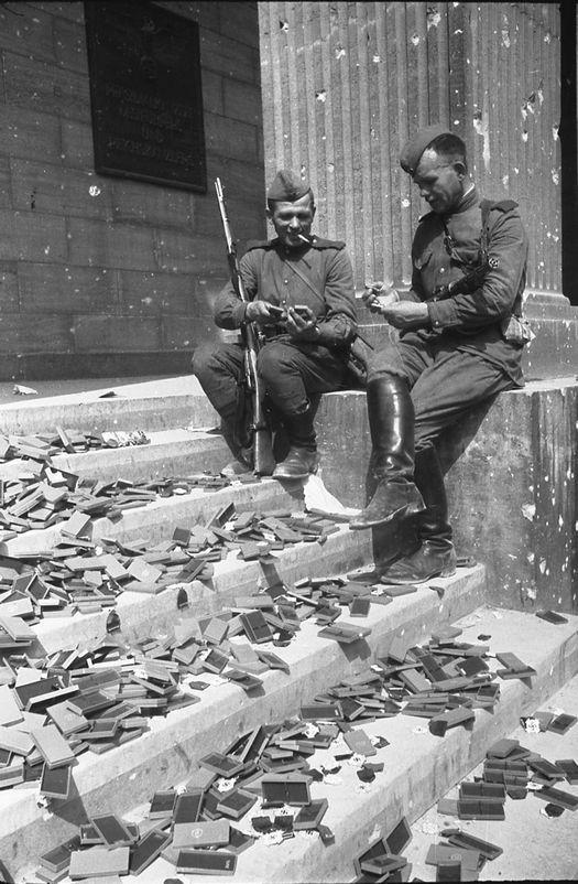 1945_szovjet_katonak_pihennek_a_berlini_reichstag_lepcsoin_mellettuk_elszorva_haborus_kituntetesek_amiket_mar_soha_nem_adnak_at_senkinek.jpg