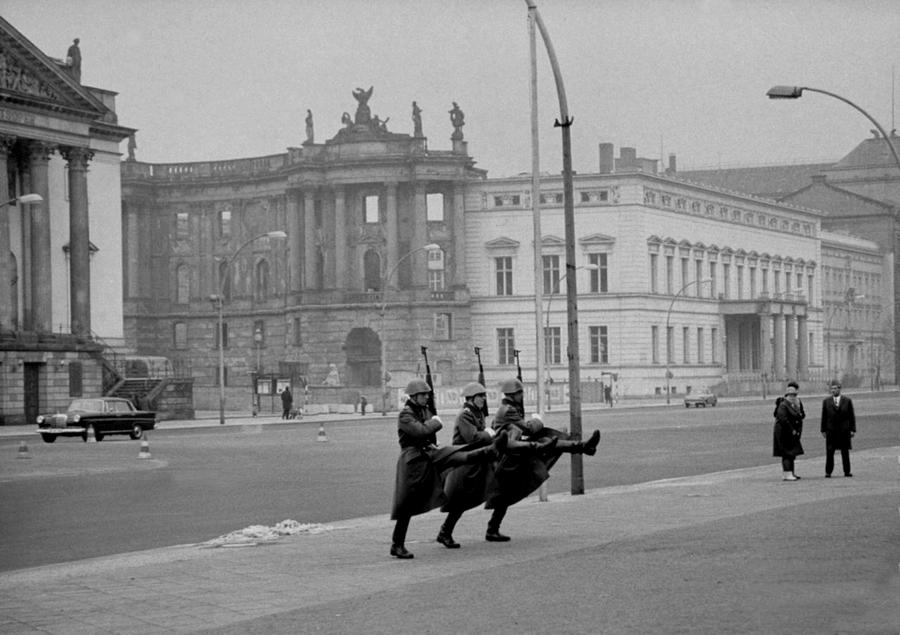 1967_kelet-berlin_katonak_diszlepesben_menetelnek_a_haborus_emlekmunel_a_hatterben_meg_egy_lebombazott_epulet_is_lathato.png