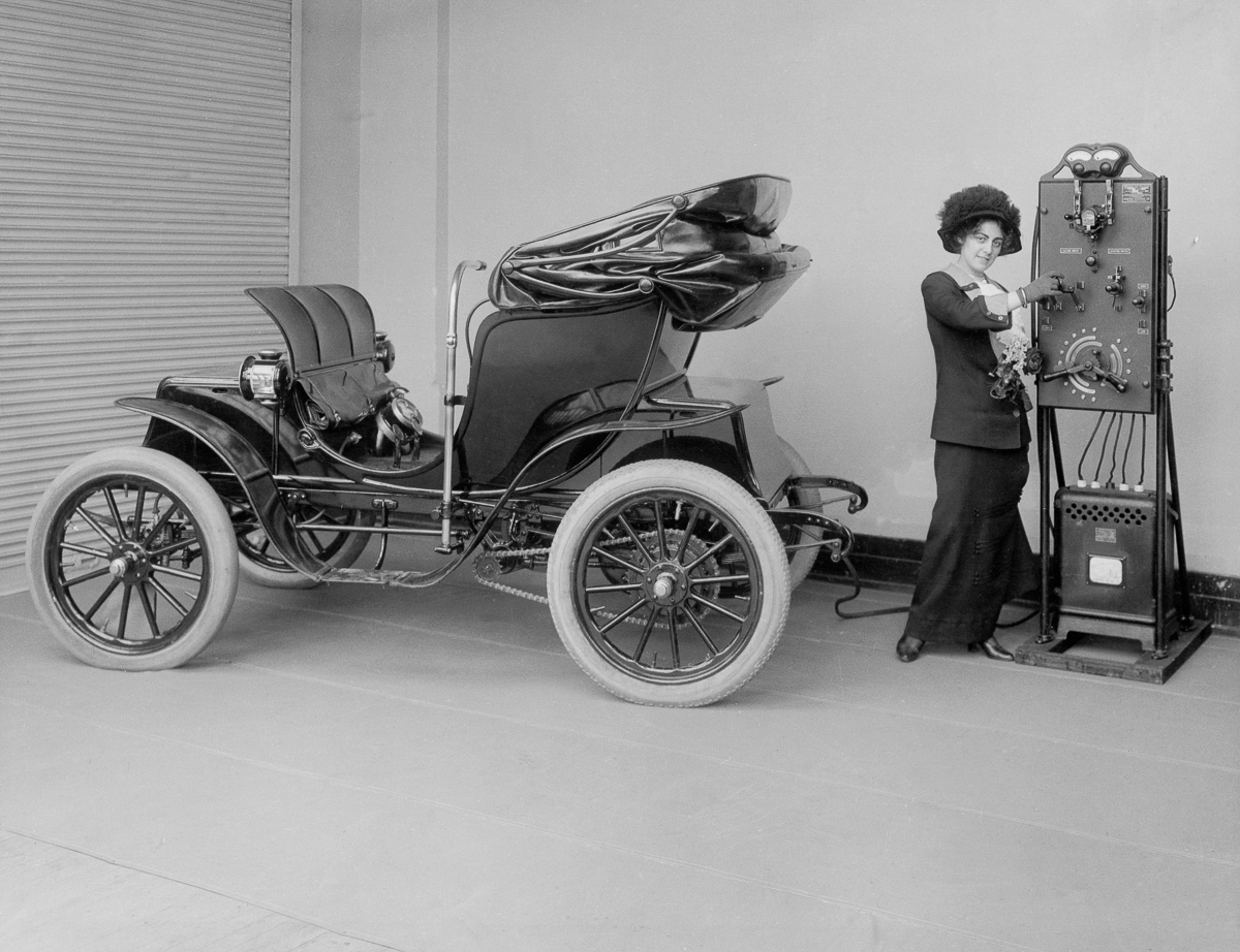 1912_a_woman_uses_a_hand_cranked_battery_charger_to_charge_her_electric_car.jpg