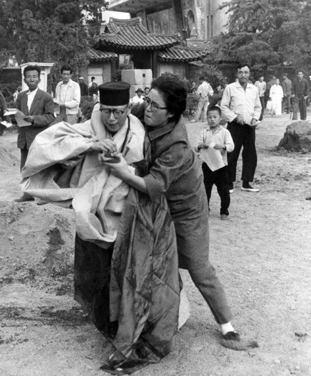 1963_egy_jarokelo_csavarja_ki_a_gyufat_az_eppen_onegetest_tervezo_buddhista_szerzetesno_kezebol_a_szouli_pagoda_parkban_del-korea.jpg