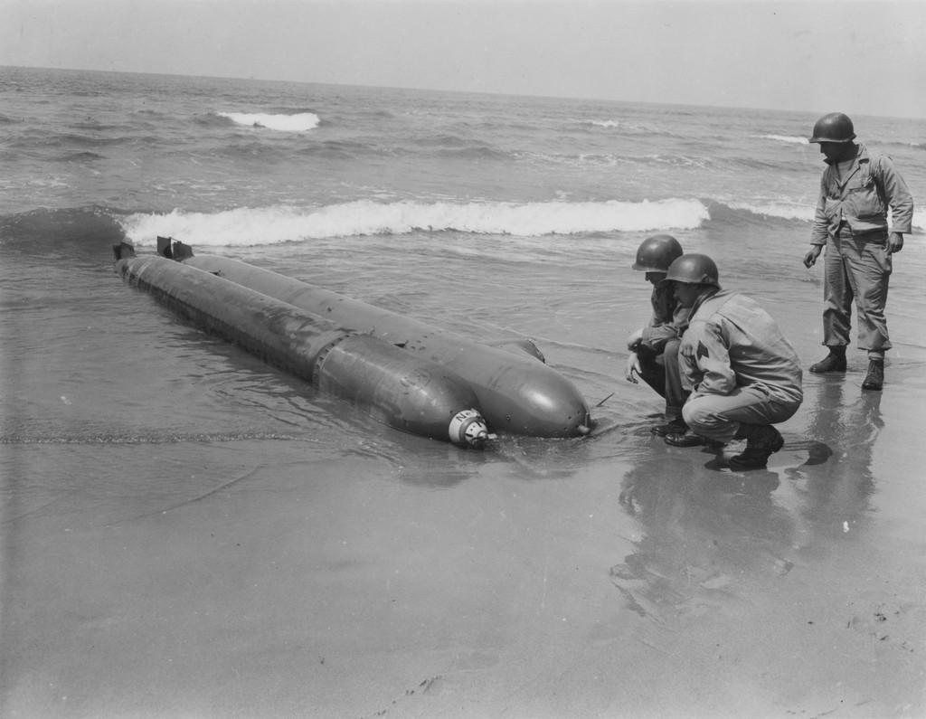 1944_amerikai_katonak_vizsgalnak_egy_oldalan_fekvo_partra_sodrodott_nemet_egyszemelyes_torpedohordozot_anzio_kozeleben_a_negernek_hivott_hadieszkoz_megbizhatatlan.jpg