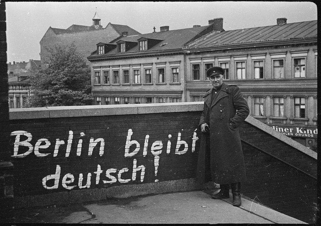 1945_majus_berlin_nemet_marad_hirdeti_a_graffiti_ami_elott_egy_szovjet_tiszt_all_a_megszallt_egykori_naci_nemetorszag_fovarosaban.jpeg
