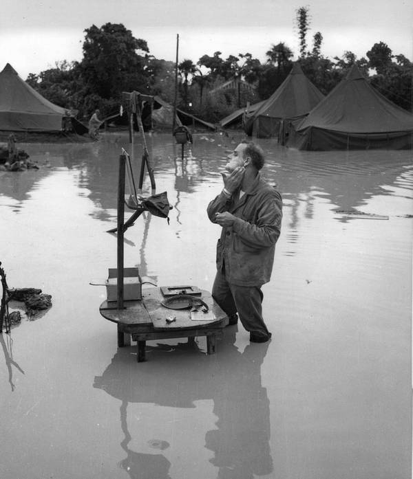 1945_majus_25_u_s_marine_corps_staff_sergeant_a_s_barnacle_shaves_in_the_flooded_campground_during_a_lull_in_the_battle_of_okinawa.jpg