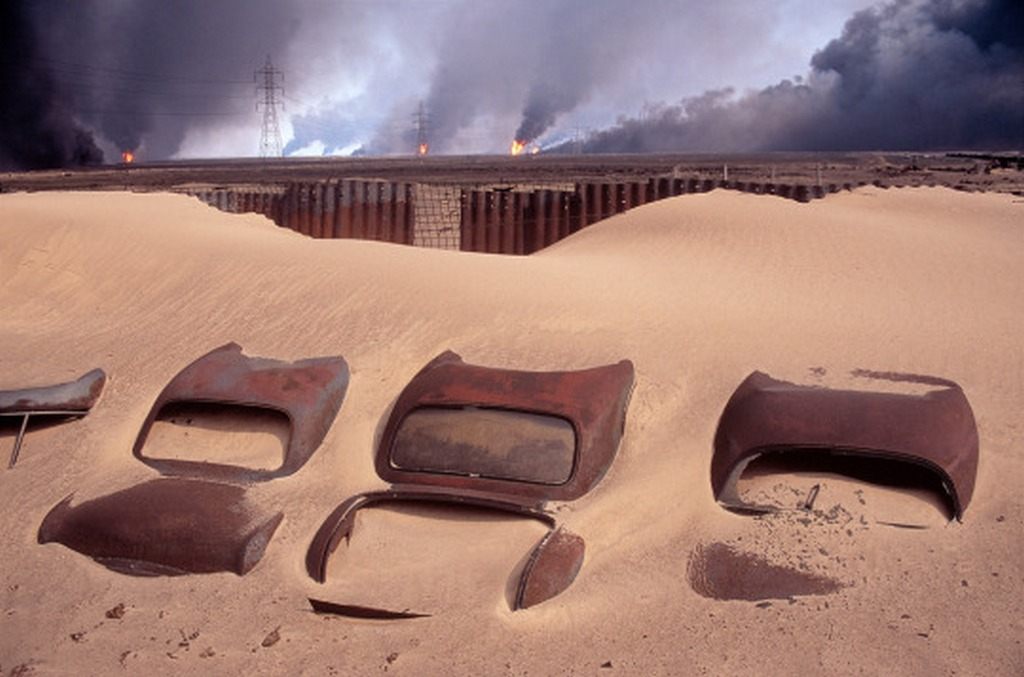 1991_kuwait_car_cemetery_in_the_background_burning_burgan_oil_fields_set_on_fire_by_retreating_iraqi_troops.jpg