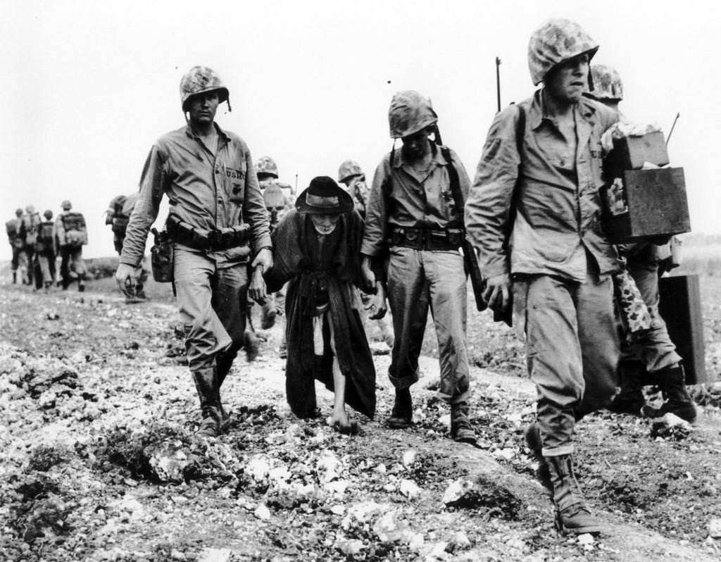 1945_junius_u_s_marines_help_escort_an_elderly_japanese_civilian_away_from_the_front_lines_during_the_battle_of_okinawa.jpg