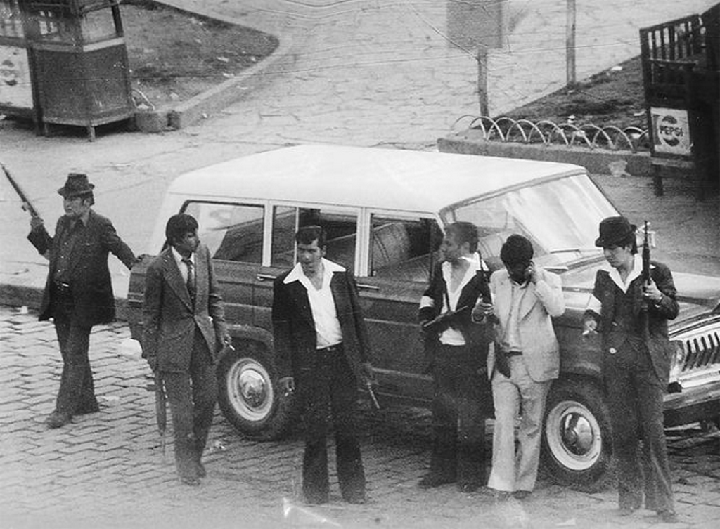 1980_julius_17_paramilitary_unit_wait_outside_an_official_vehicle_allegedly_used_to_kidnap_their_victims_during_bolivian_coup_d_etat.png