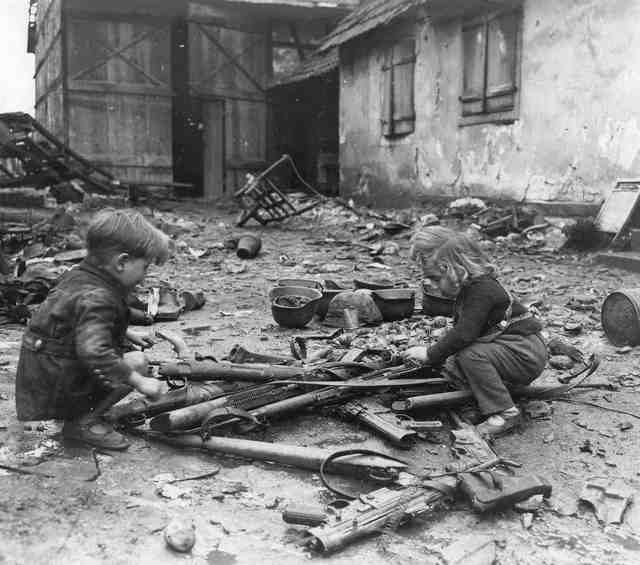 1945_majus_children_play_amid_weapons_abandoned_in_ruins_of_nazi_germany.jpg