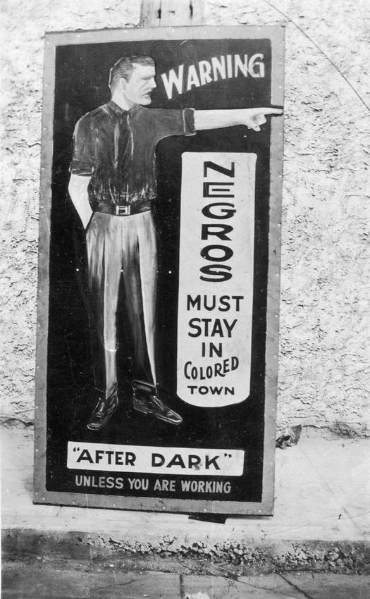 1940s-50s_negro_warning_sign_to_stay_away_from_white_area_crudely_painted_white_man_points_toward_colored_town_cr.jpg