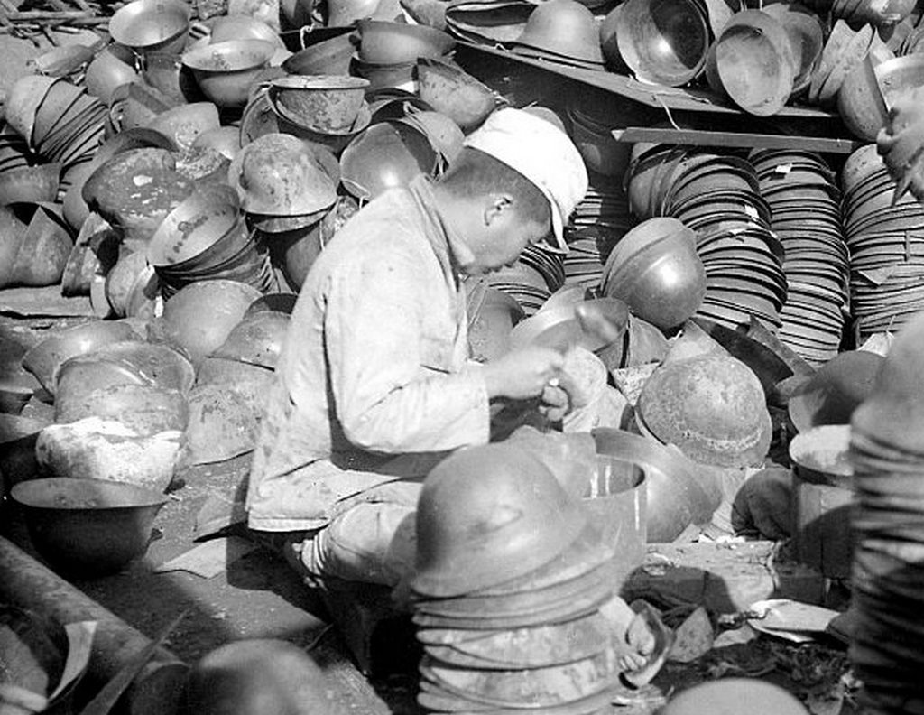 1945_meanwhile_at_roughly_the_same_time_on_the_other_side_of_the_world_a_young_japanese_hired_by_the_us_army_cleans_and_stacks_m30-32_tetsu-bo_helmets.jpg