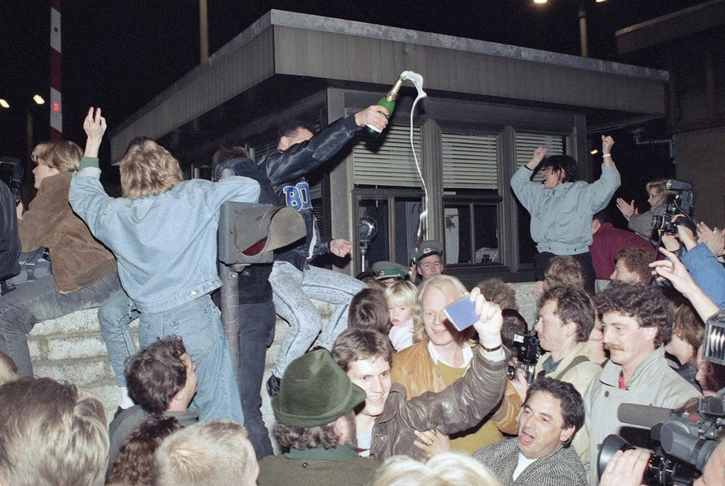 1989_berliners_celebrating_on_top_of_the_wall_as_east_germans_flood_through_the_dismantled_berlin_wall_into_west_berlin.jpg