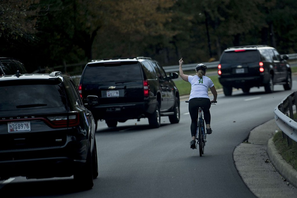 2017_10_28_juli_briskman_riding_her_bike_gestures_with_her_middle_finger_as_a_motorcade_carrying_president_donald_trump_departs_trump_national_golf_course_in_sterling_virginia.jpg