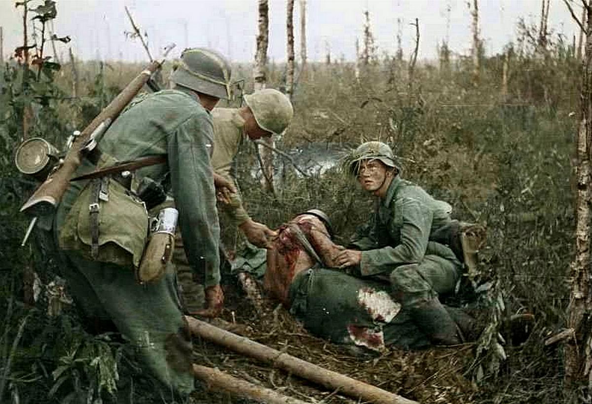 1943_julius_volkovi_utkozet_leningrad_kozeleben_szovjet_hadifogoly_segit_ellatni_egy_sebesult_nemet_katonat_szinezte_wwiicolorizer_bill.png