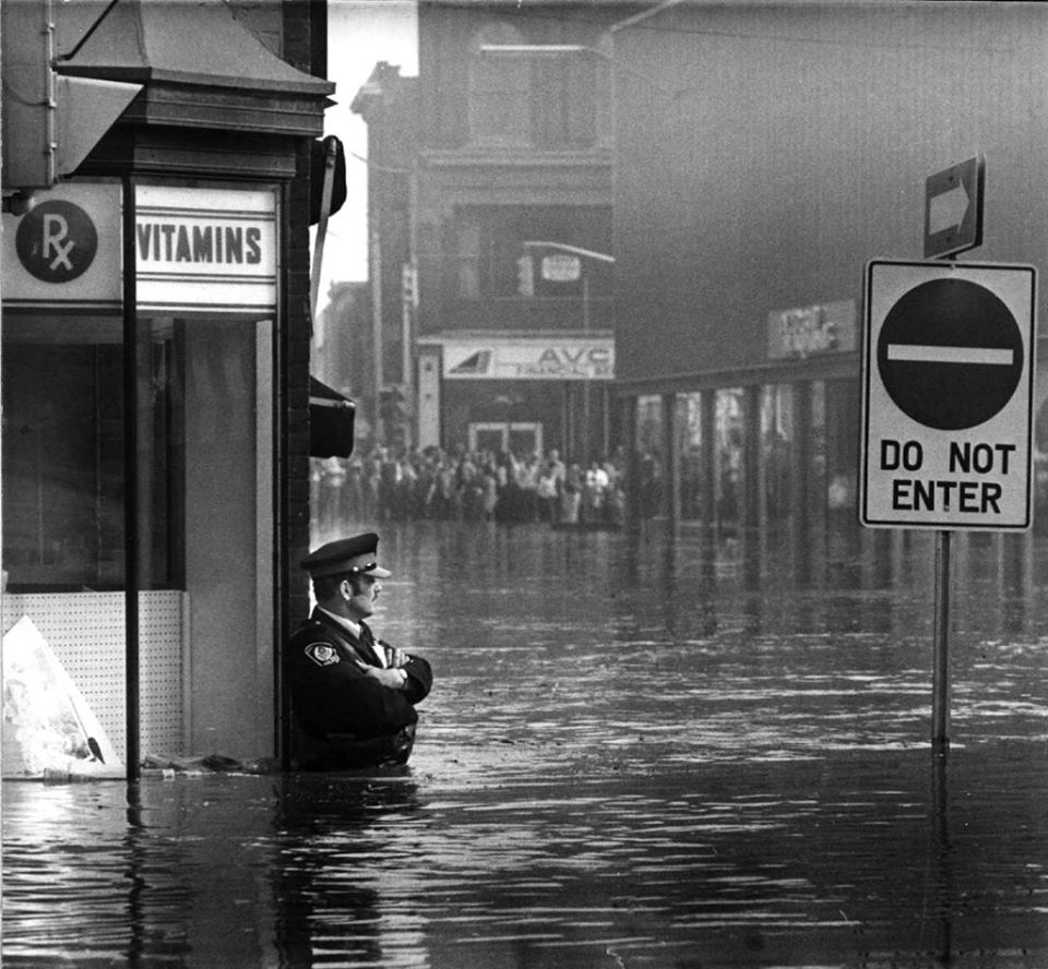 40_amazing_historical_pictures_police_officer_guarding_a_pharmacy_in_high-flood_waters_ontario_1974.jpg