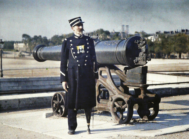 a_soldier_in_uniform_with_three_medals_stands_next_to_a_cannon_in_paris_in_1918_his_left_leg_has_been_replaced_by_an_artificial_limb_r_schultz_collection_the_image_works.jpg
