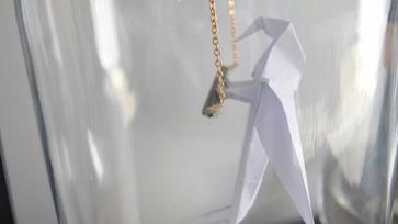Üvegkalitkába zárt origami papagáj
