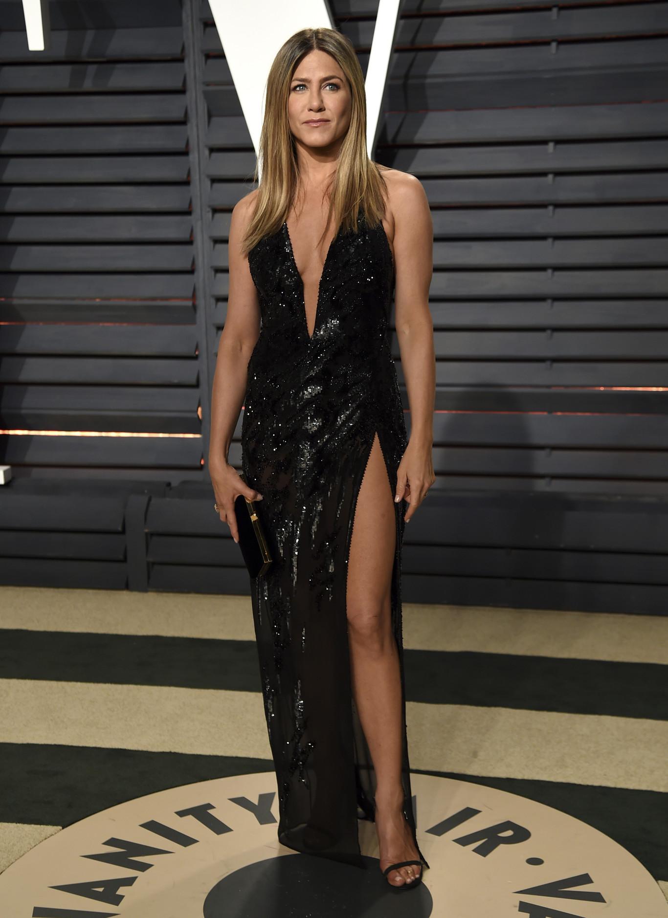 Jennifer Aniston mélyen dekoltált, merészen sliccelt, fekete Atelier Versace estélyiben.