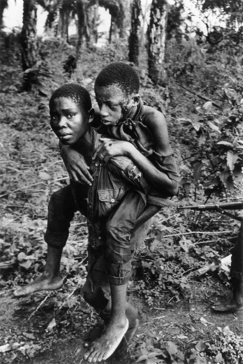 Arcán sebesült bajtársát menti ez a biafrai gerilla