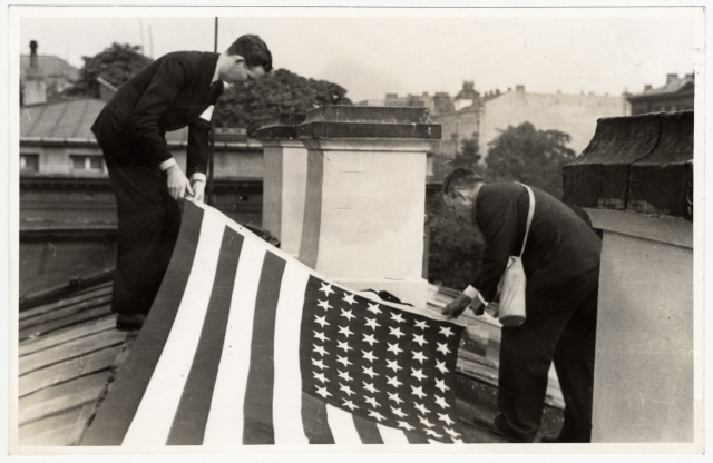 A nagykövetség tetejére kifeszítik az amerikai lobogót, hogy a német bombázók beazonosíthassák és ne bombázzák