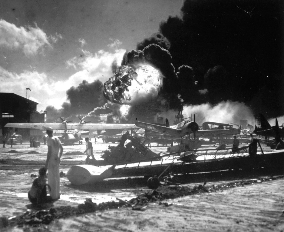 december_7_1941_sailors_stand_among_wrecked_airplanes_at_ford_island_naval_air_station_as_they_watch_the_explosion_of_the_uss_shaw_in_the_background.jpg
