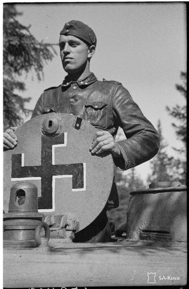 Finn harckocsizó egy T-34 búvónyílásában. A fedélen félszárú, fehér árnyékú fekete horogkereszt.