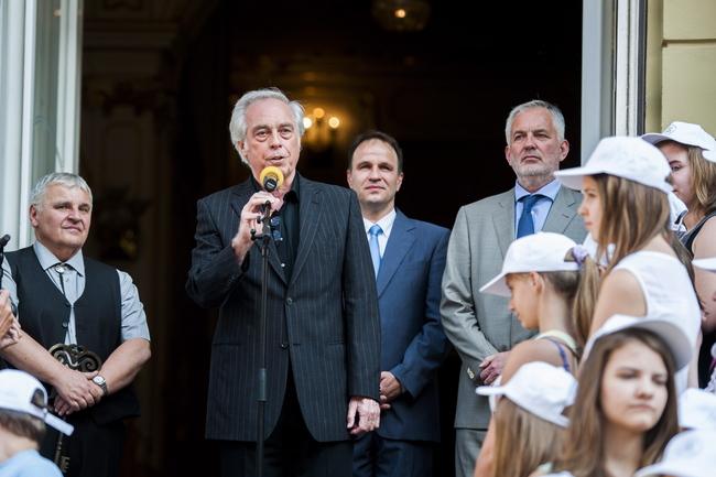 Huszti Péter Kossuth-díjas színész beszél a Pécsi Országos Színházi Találkozó megnyitóján. Mögötte jobbra Rázga Miklós, a Pécsi Nemzeti Színház igazgatója és Páva Zsolt, Pécs polgármestere, balról Stenczer Béla fesztiváligazgató