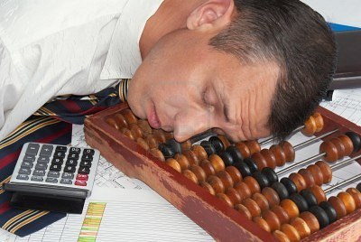 8277923-the-tired-engineer-smetchik-has-fallen-asleep-directly-on-abacus-after-the-heavy-working-day.jpg