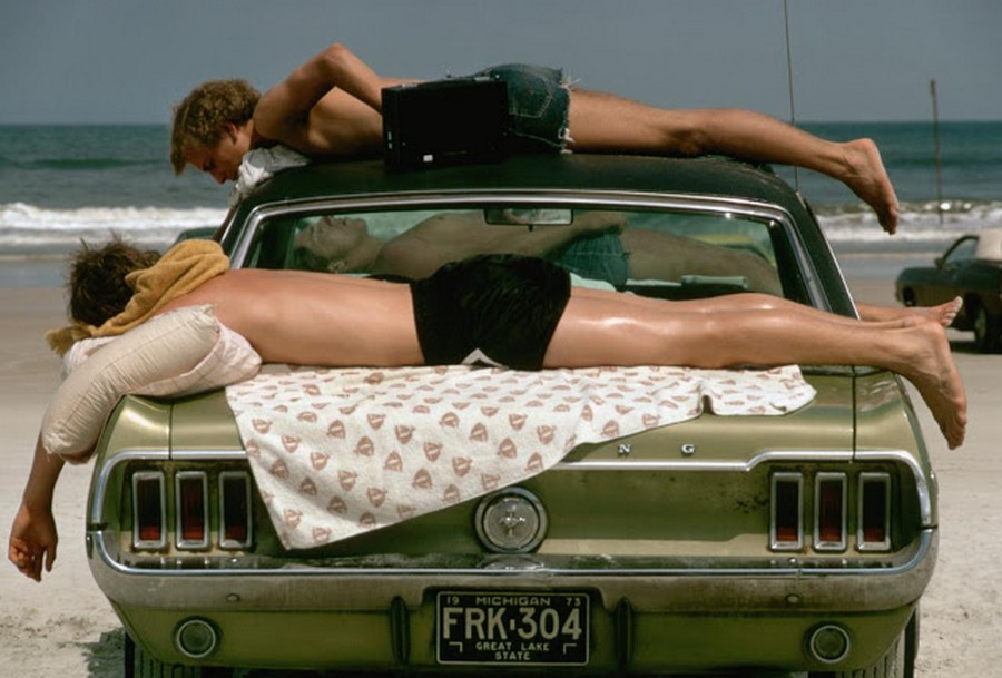 1973_three_young_men_sunbathe_on_a_green_ford_mustang_on_daytona_beach_1973.jpg