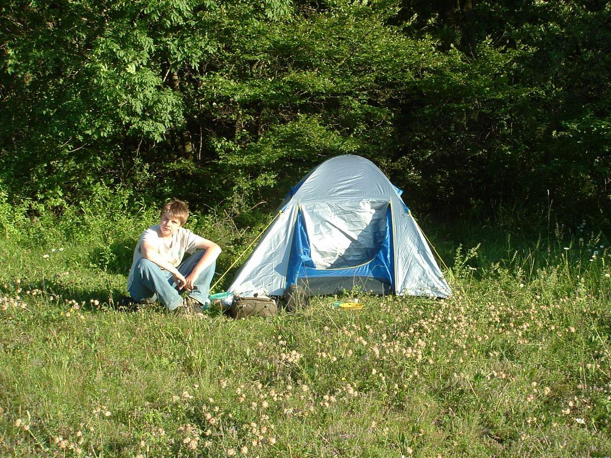 A fiam üldögél a felütött sátor mellett Jásd felett a legelők felső szélén. Itt is az Országos Kéktúrát jártuk...