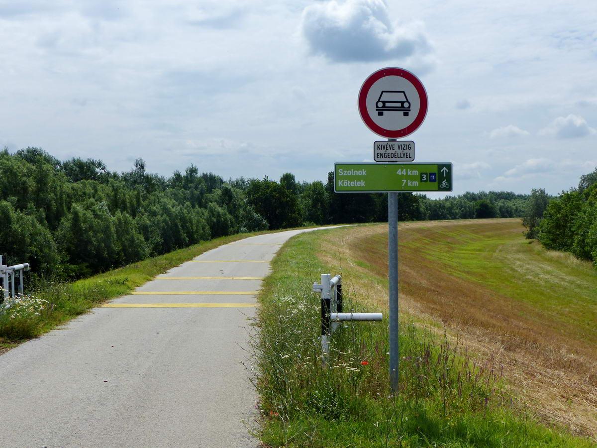 Információs tábla áll ott, ahol a komptól jövő aszfaltút keresztezi a Tisza-gátat. 44 kilométerre taksálta a gáton a Szolnokig vezető út hosszát.
