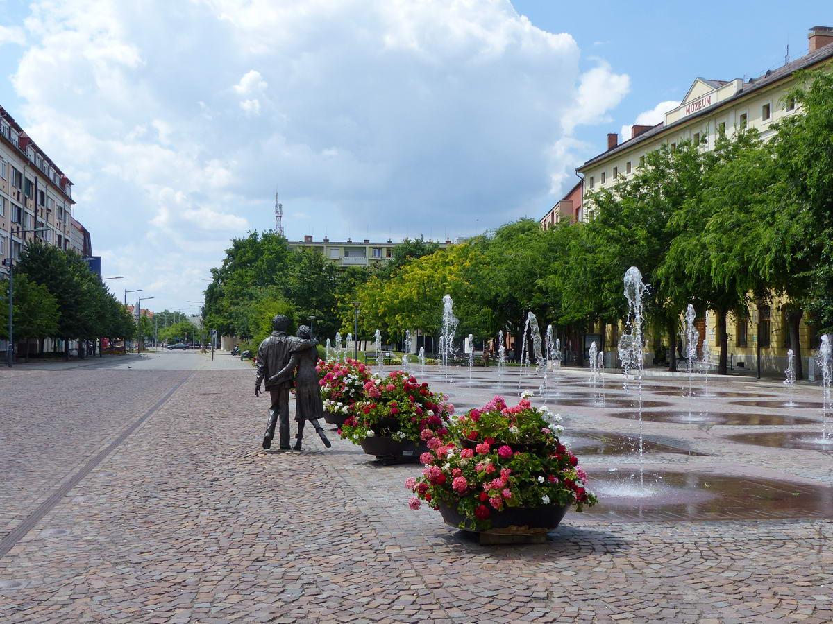 Szökőkutak a szolnoki Kossuth téren az andalgó diákpár szobrával (Fiatal pár farmerben, Kligl Sándor alkotása)