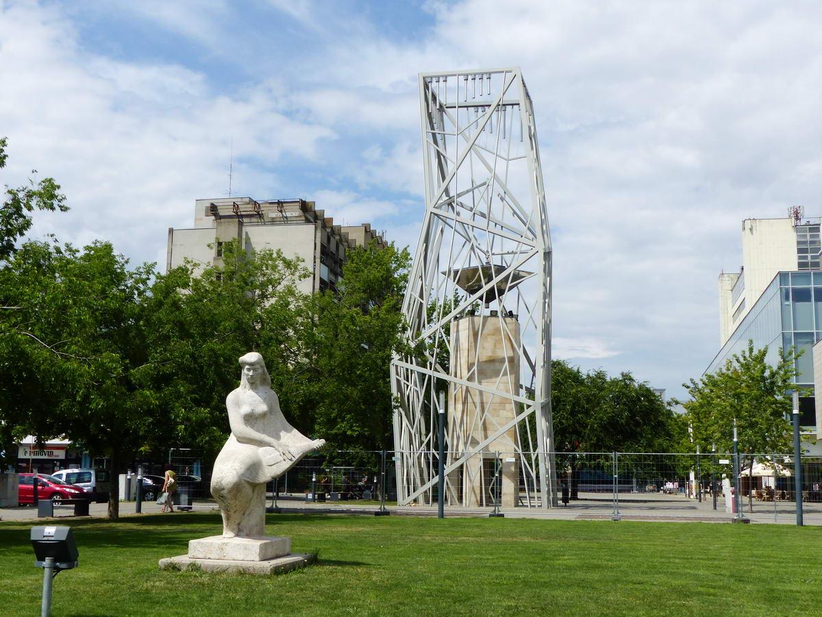 Harangtorony az út mellett, előtte a Mandolinos nő (avagy Zenélő) szobrával (Nagy István alkotása)