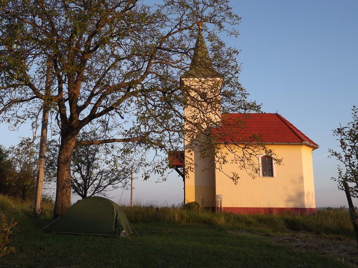 Egy kis kápolna és a sátor a lemenő nap fényében Rádiháza felett a dombtetőn