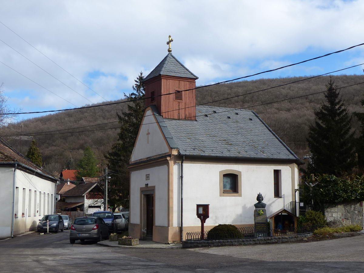 Kis Szűz Mária kápolna áll Pilisszentlászló főterén. Mellette a településnek nevet adó Szent László király mellszobra látható.