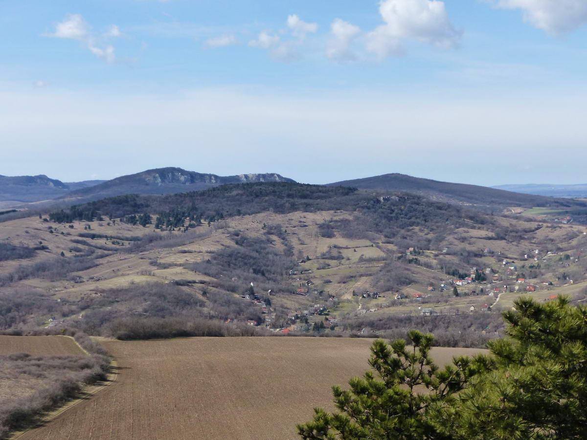 Nyugatra már jól látható a sziklás homlokú Kő-hegy, alatta a Tokodi pincék völgye fekszik a szőlőskertekkel