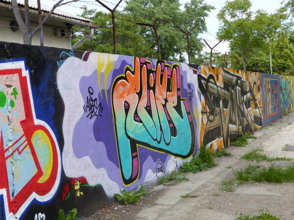 Szinte már ikonikus graffitis fal a HÉV sínjei mellett a Filatorigát megállónál