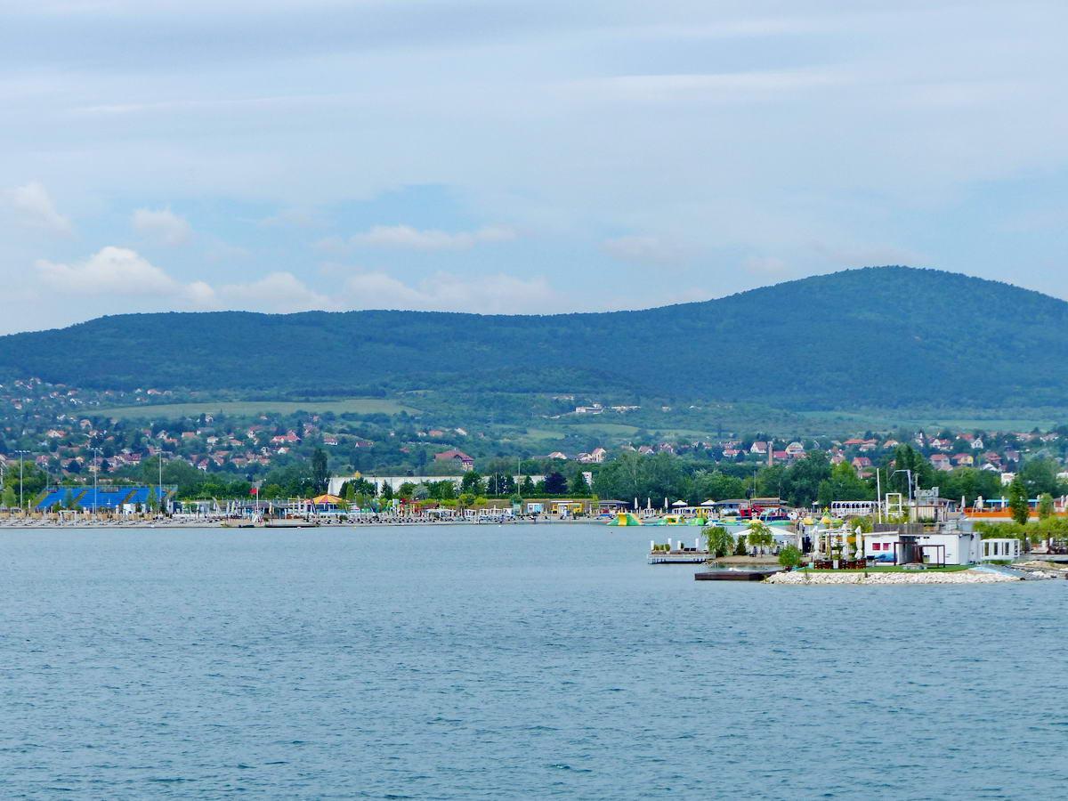 Az utóbbi időben eléggé kiépült a Lupa-tó. Mögötte a Kevély vonulata húzódik, jobbra a Nagy-Kevéllyel (534 m)