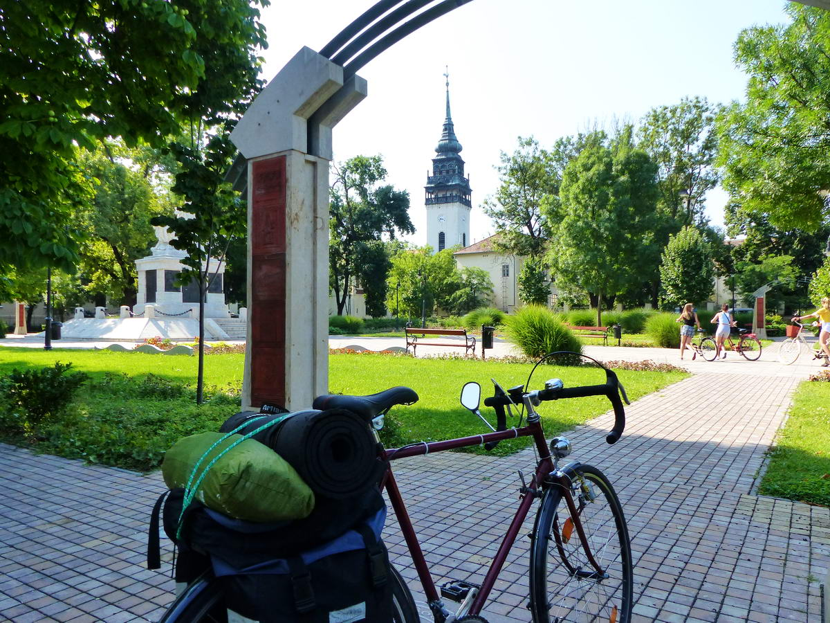 Megálltam egy pihenőre a Hősök tere parkjában. A háttérben feltűnik a református templom tornya.