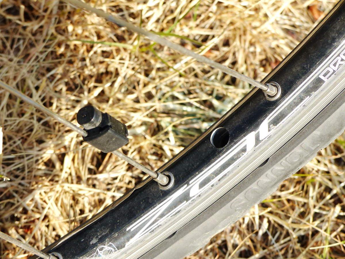 A figyelmes szemlélő csak annyit vesz észre, hogy nincs szelep a keréken. A küllőn a kerékpárcomputer mágneses jeladója látható.