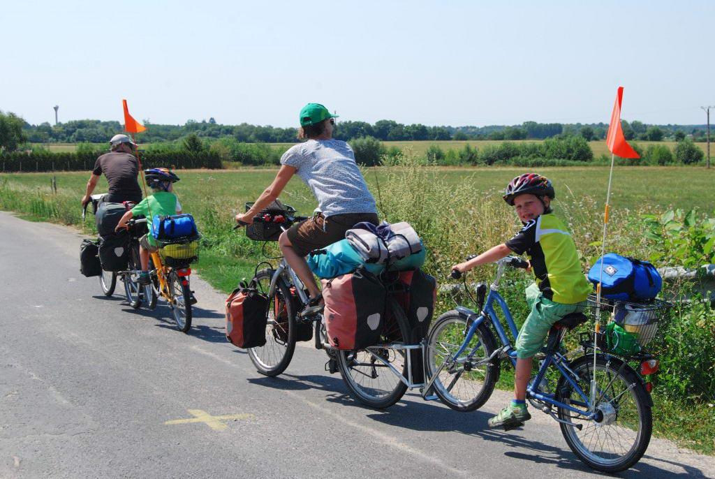 [08] Túrázik a család. Figyelemre méltó a gyerekek kerékpárjainak elhelyezése. Hozzá vannak rögzítve a nagy kerékpárokhoz, tehát nem tudnak csalinkázni az úton, viszont ha tekernek, azzal segíthetik a haladást.