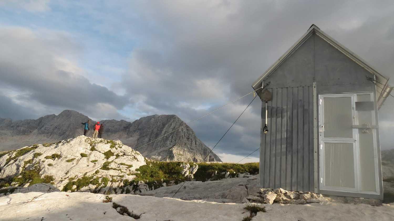 Zoli, Erik és Bori és a menedékház a táborunk felett 20percnyi járásra, az első napi cuccolás végén (Szabó Joci képe)
