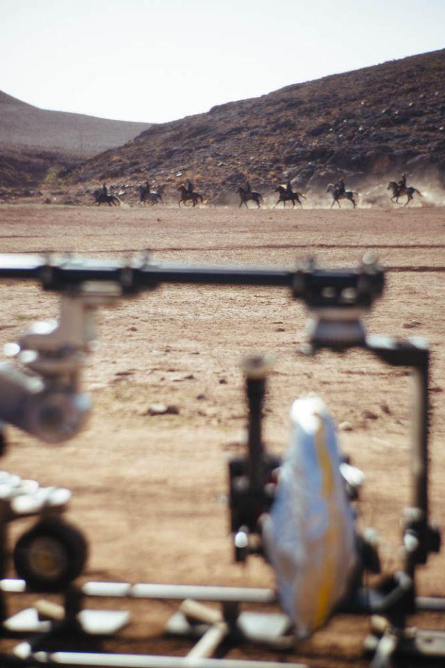 Vágtázó lovasok szelik át a sivatagot.