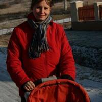 Nő piros kabátban, babakocsival
