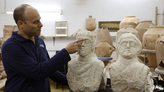 israeli-archaeologist-eitan-klein-of-the-israel-antiquities-authority-shows-off-two-late-roman-busts-unearthed-near-the-ancient-city-of-beit-shean-following-a-chance-find-by-a-woman-walker-1546174345960-2.jpg