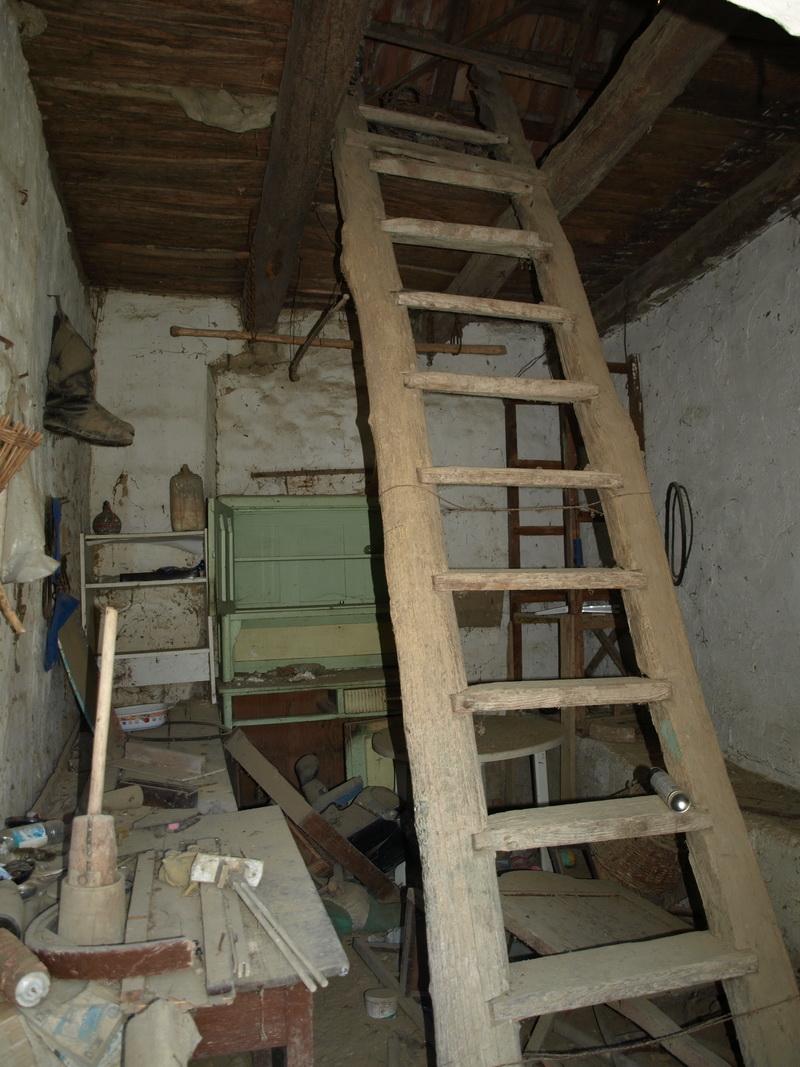 Padlásfeljáró, régi lomokkal és használati tárgyakkal, eszközökkel teli helyiségben