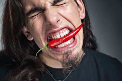 5216184-young-caucasian-man-with-a-red-hot-chili-pepper-in-his-mouth.jpg